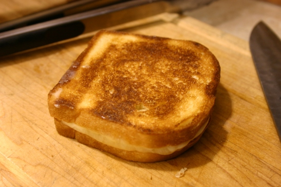 A grilled cheese sandwich on a wooden cutting board, next to a knife. Creative Commons image by Mack Male on Flickr.